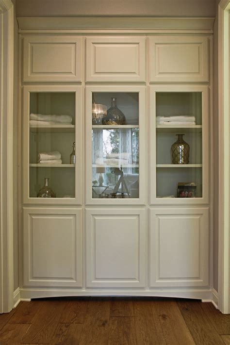 Burrows Cabinets' floor-to-ceiling linen cabinets w glass